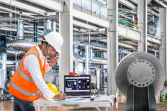 Engineer using laptop computer in thermal power plant factory.  royalty free stock image