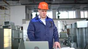 Engineer is Using Laptop in Industrial Environment. slow-motion. Engineer is Using Laptop in Industrial Environment stock video footage