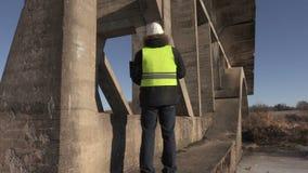 Engineer using laptop under the bridge. In winter day stock video