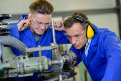 Engineer using machine apprentice with fingers in ears Royalty Free Stock Photos