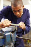 Engineer Using Metal File On Factory Floor. Concentrating stock photography
