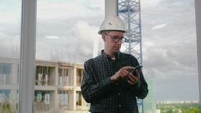 Engineer using mobile phone in helmet. Medium shot.Engineer using mobile phone in helmet. Professional shot in 4K resolution. 025. You can use it e.g. in your stock video footage