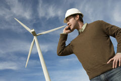 Engineer Using Mobile Phone At Wind Farm. Low angle view of a male engineer using mobile phone at wind farm Royalty Free Stock Photo