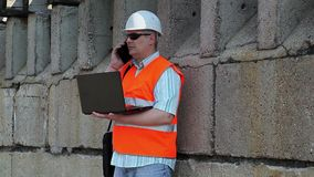 Engineer using phone and laptop near wall. In summer day stock video footage