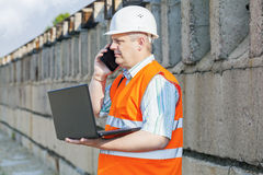 Engineer using phone and laptop near wall Stock Images