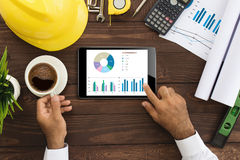 Engineer using tablet checking business graph on table Royalty Free Stock Image