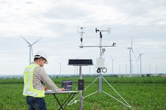 Engineer using tablet computer collect data with meteorological. Instrument to measure the wind speed, temperature and humidity and solar cell system on corn stock photos