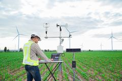 Engineer using tablet computer collect data with meteorological instrument to measure the wind speed, temperature and humidity and. Solar cell system on corn royalty free stock images
