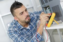Engineer using voltage and current tester. Engineer using a voltage and current tester Royalty Free Stock Image