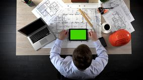 Engineer viewing online layout of building project, using green screen tablet. Stock photo Royalty Free Stock Photo