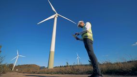 Engineer walks in a field near windmills, holding a tablet. Alternative energy concept. stock footage