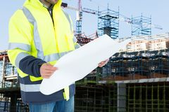 Engineer watching plans on construction site. Digital composite of engineer at  construction  site Stock Image