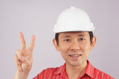 Engineer wear red shirt and white hat make signal victory. Engineer wear red shirt and white engineer hat make signal by victory on white background Royalty Free Stock Photos