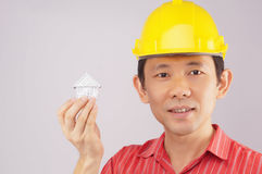 Engineer wear red shirt and yellow engineer hat holding house Royalty Free Stock Images