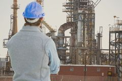 Engineer wearing blue safety helmet is looking at oil refinery from the back against oil refinery ba Stock Images