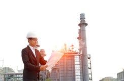 Engineer wearing white helmet holding paper drawing Stock Photo