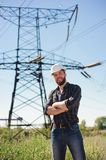 Engineer with white hard hat under the power lines. Engineer work at an electrical substation. stock photo