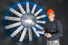 Engineer in a Wind tunnel. A smiling engineer, wearing a hardtop, protective goggles and earplugs in a wind tunnel, completing his inspection Stock Photos