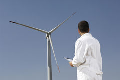 Engineer and wind turbines. Man and wind turbines; electronics engineer checking wind turbines, concept of alternative energy and ecology Royalty Free Stock Images