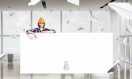 Engineer woman with banner. Young woman builder wearing helmet and holding blank banner Royalty Free Stock Images
