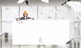 Engineer woman with banner. Young woman builder wearing helmet and holding blank banner Royalty Free Stock Photos