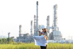 Engineer woman holding blueprint with radio for workers security control at power plant energy and petrochemical industry. Royalty Free Stock Photography