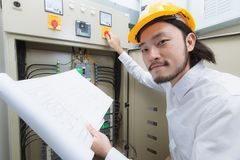 Engineer at work. Close up of young Asian electric engineer in beige pant and white shirt, wear yellow helmet, squat near control panel, working instruction in stock photography