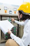 Engineer at work. Close up of young Asian electric engineer in beige pant and white shirt, wear yellow helmet, squat near control panel, working instruction in stock photo