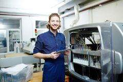 Engineer at work. Portrait of smiling young engineer standing near the printing machine stock photography