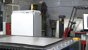 Engineer worker adjusts iron sheet for cutting metal plate on CNC laser machine. On industrial manufacture stock footage