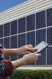 Solar energy, worker hands using tablet and panels. Engineer or worker calculate energy saving using tablet with solar panels in background, closeup of tablet Royalty Free Stock Image