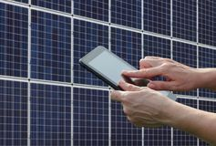 Solar energy, worker hands using tablet and panels. Engineer or worker calculate energy saving using tablet with solar panels in background, closeup of tablet Stock Photography