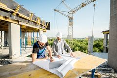 Engineer with worker at the construction site. Engineer with worker in uniform working with architectural drawings and laptop at the table on the construction royalty free stock images