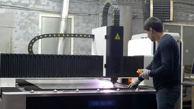 Engineer worker controls the cutting of metal plates. On metal manufacture stock video