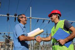 Engineer and Worker at Electrical Substation. Smiling workers with blueprints and clipboard in meeting at electrical substation. Selective focus stock images