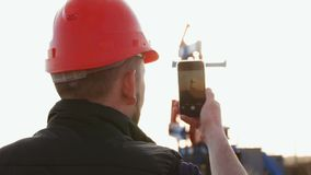 Engineer worker on an oil rig take photo with smartphone. Oil industry using mobile phone communication.