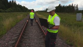 Engineer and worker on railway track. In summer day stock video