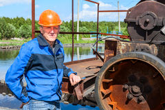 Engineer worker stands near sewage treatment mechanism Royalty Free Stock Photo