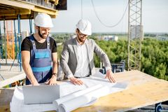 Engineer with worker at the construction site. Engineer with worker in uniform working with architectural drawings and laptop at the table on the construction royalty free stock photo