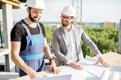 Engineer with worker at the construction site. Engineer with worker in uniform working with architectural drawings and laptop at the table on the construction stock photo