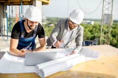 Engineer with worker at the construction site. Engineer with worker in uniform working with architectural drawings and laptop at the table on the construction stock images