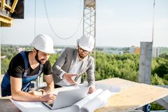 Engineer with worker at the construction site. Engineer with worker in uniform working with architectural drawings and laptop at the table on the construction stock photography