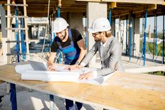 Engineer with worker at the construction site. Engineer with worker in uniform working with architectural drawings and laptop at the table on the construction stock photos