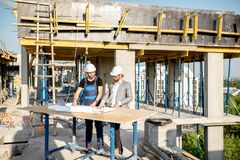 Engineer with worker at the construction site. Engineer with worker in uniform working with architectural drawings at the table on the construction site outdoors stock photography