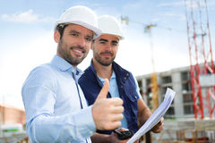 Engineer and worker watching blueprint on construction site Stock Photo