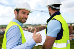 Engineer and worker watching blueprint on construction site Stock Photography