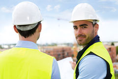 Engineer and worker watching blueprint on construction site Royalty Free Stock Photography
