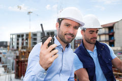 Engineer and worker watching blueprint on construction site Royalty Free Stock Image