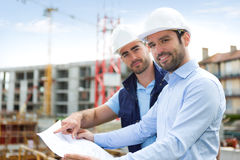 Engineer and worker watching blueprint on construction site Royalty Free Stock Photo