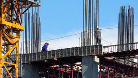 Engineer and workers on high building construction site. Royalty Free Stock Photo